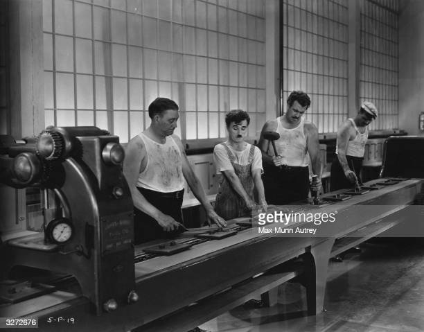 British comic actor and director Charles Chaplin working on a factory production line in a scene from 'Modern Times' directed by himself