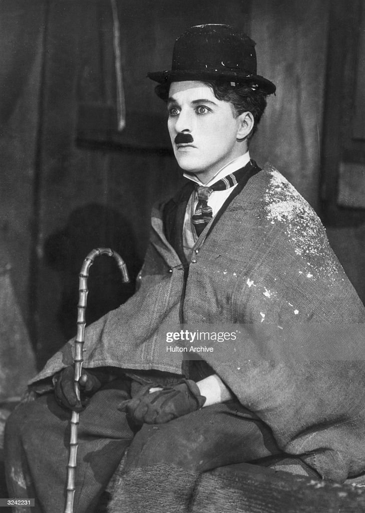 British comic actor and director Charlie Chaplin (1899 - 1977), as the Little Tramp, wearing a burlap shawl in a still from 'The Gold Rush' directed by Chaplin.