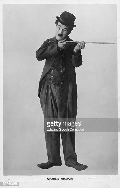 British comic actor and film director Charlie Chaplin takes aim with his walking stick in character as the Little Tramp circa 1925