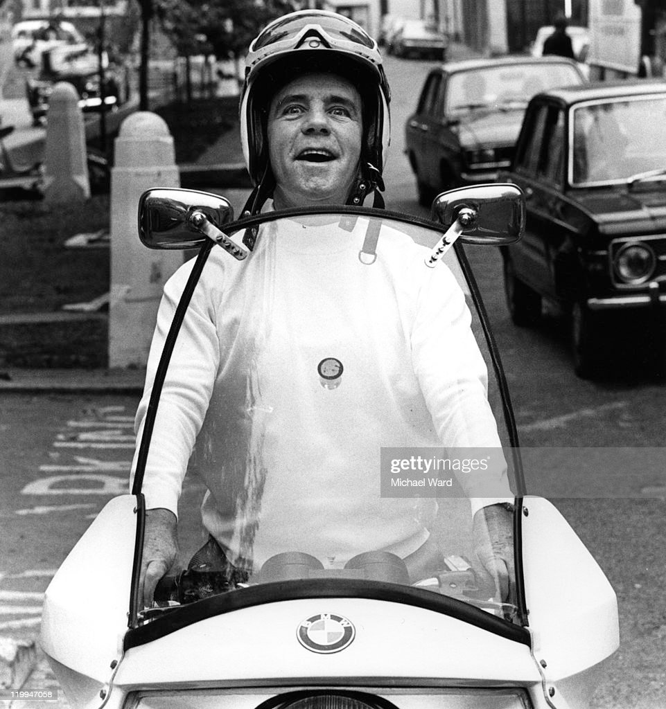 British comic actor Norman Wisdom on a moped, 1975.