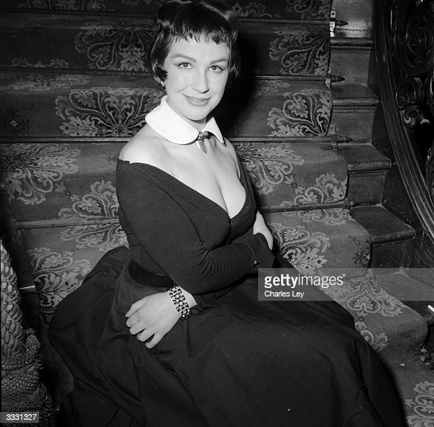 British comic actress Fenella Fielding sitting on a staircase
