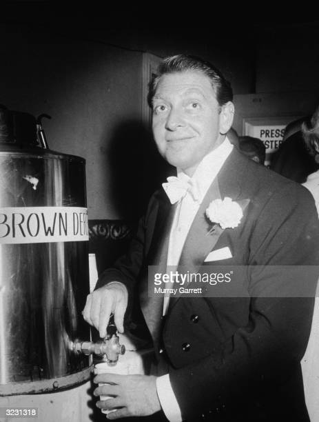 British composer and conductor David Rose pours himself a cup of coffee backstage at the Academy Awards Los Angeles California The coffee is labeled...