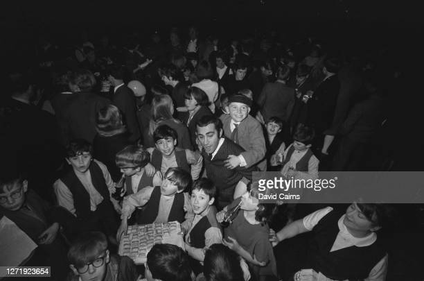 British composer Lionel Bart with brothers Arthur and Jack Wild, who are starring in his stage musical 'Oliver!', and a crowd of boys from London...