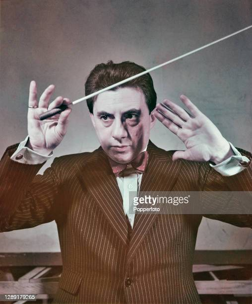British conductor and musician John Barbirolli posed conducting with a baton in England in 1948.