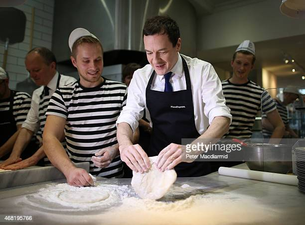 British Conservative Chancellor George Osborne prepares a pizza as he visits a Pizza Express restaurant on March 31 2015 in Hove England Campaigning...