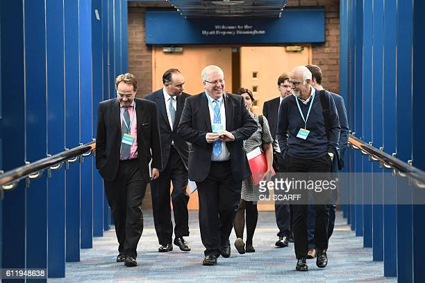 British Conservative Party Chairman and Chancellor of the Duchy of Lancaster Patrick McLoughlin walks along the bridge from the hotel to the...