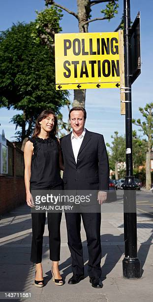 British Conservative party leader David Cameron accompanied by his wife Samantha arrive at a polling station in west London on June 4 before casting...