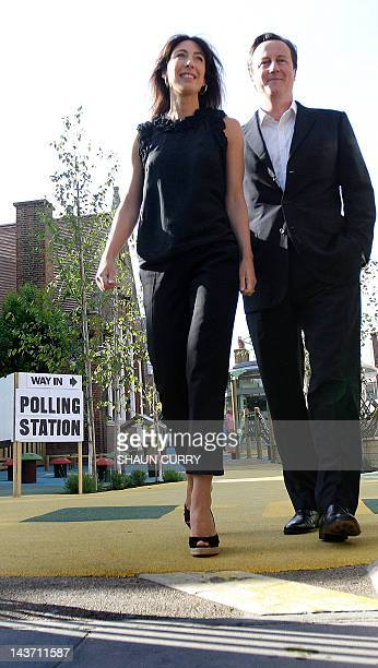 British Conservative party leader David Cameron accompanied by his wife Samantha leave a polling station in west London on June 4 after casting their...
