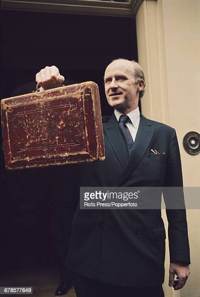 British Conservative Party politician and Chancellor of the Exchequer Anthony Barber holds up the Chancellor's battered red Gladstone's Budget Box on...