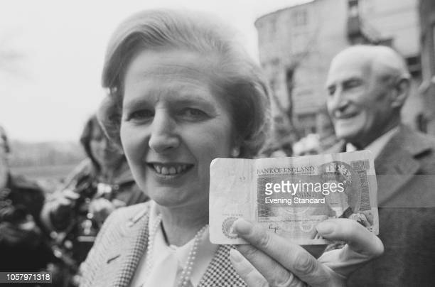 British Conservative Party politician and Leader of the Opposition Margaret Thatcher holding a Bank of England £1 note, UK, 27th April 1979.