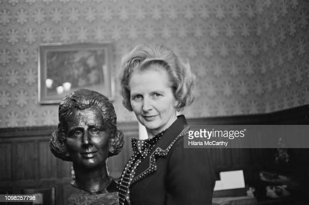 British Conservative Party politician and Leader of the Opposition Margaret Thatcher with her bronze bust by artist Beatrice Murray, UK, 13th...
