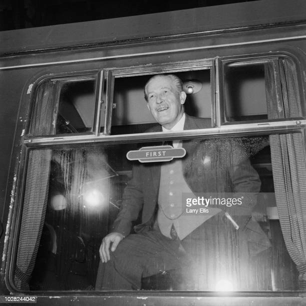 British Conservative Party politician and Prime Minister of the United Kingdom Harold Macmillan pictured standing at the window of a first class...