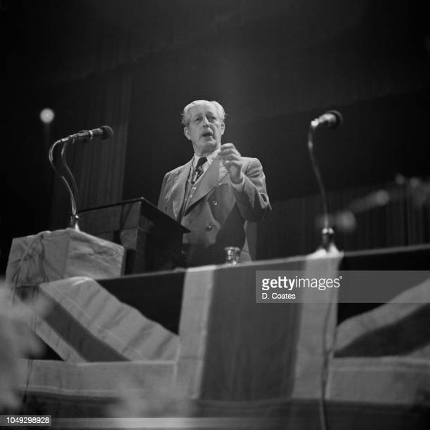 British Conservative Party politician and Prime Minister of the United Kingdom Harold Macmillan delivers a speech from a union flag bedecked platform...