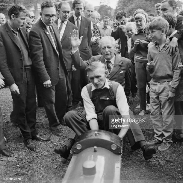 British Conservative Party politician and Prime Minister of the United Kingdom Harold Macmillan pictured hitching a ride behind a miniature steam...