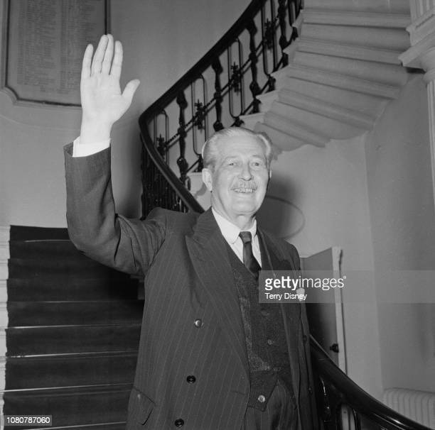 British Conservative Party politician and Prime Minister of the United Kingdom Harold Macmillan waves from the bottom of the staircase during a visit...