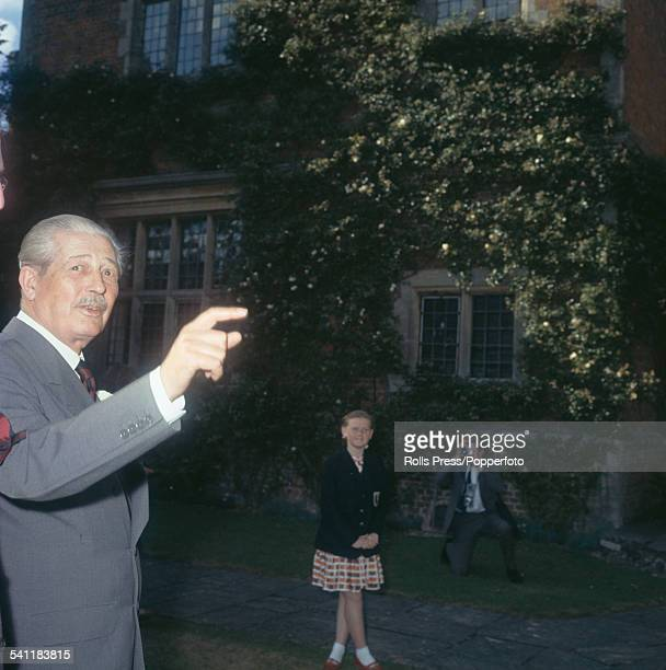 British Conservative Party politician and Prime Minister of the United Kingdom Harold Macmillan pictured in front of an historic house circa 1962