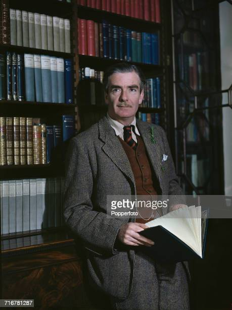 British Conservative Party politician and Secretary of State for Foreign Affairs, Anthony Eden posed standing next to a bookcase in his office circa...