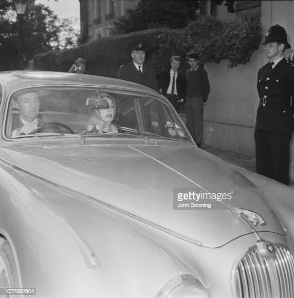 British Conservative Party politician John Profumo pictured driving his wife actress Valerie Hobson in his Jaguar car in London on 19th June 1963...