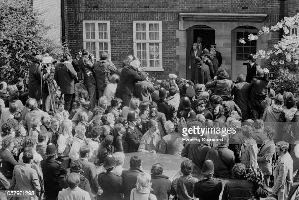 British Conservative Party politician Margaret Thatcher exiting her house with her husband Denis to meet the press and fans following her victory in...