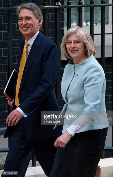 British Conservative party's Transport Secretary, Philip Hammond, and Home Secretary, Theresa May, arrive for the first Cabinet meeting of the new...