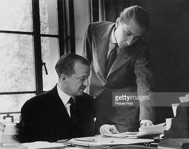 British Conservative politician Afred Duff Cooper, 1st Viscount Norwich , the Minister of Information, at his office, 1940. His secretary is handing...