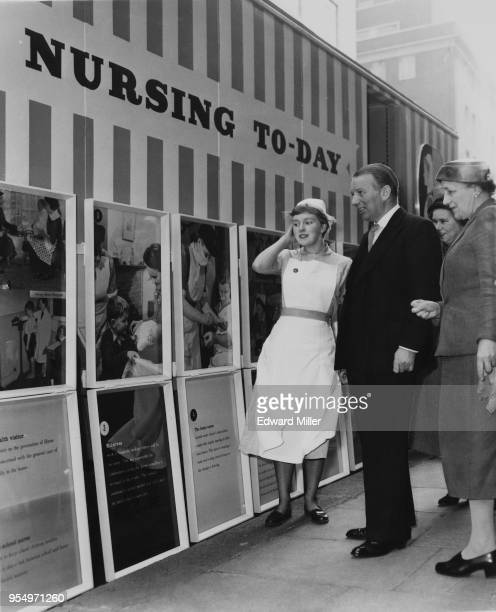 British Conservative politician Derek WalkerSmith the Minister of Health views a series of photographs depicting 'Nursing Today' at the mobile...