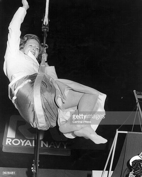 British Conservative prime minister Margaret Thatcher swinging from a hoist during a visit to the Royal Navy Original Publication People Disc HW0277