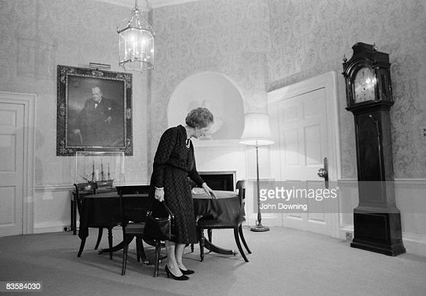British Conservative prime minister Margaret Thatcher wipes crumbs off the table at 10 Downing Street London circa 1990 A painting of her predecessor...