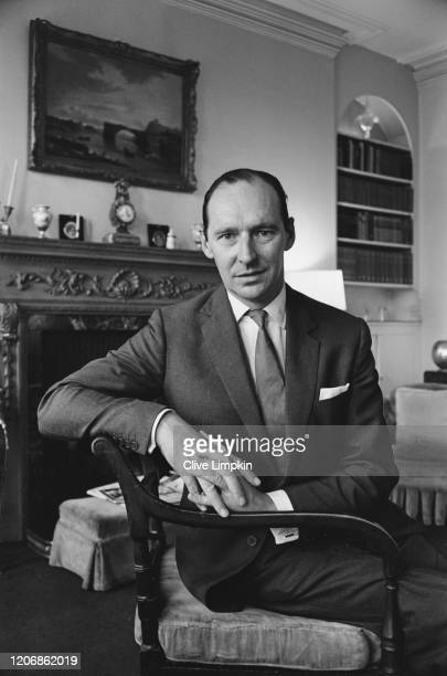 British Conservatve Party politician and diplomat David OrmsbyGore 5th Baron Harlech sits with his hands clasped together resting on the arm of his...
