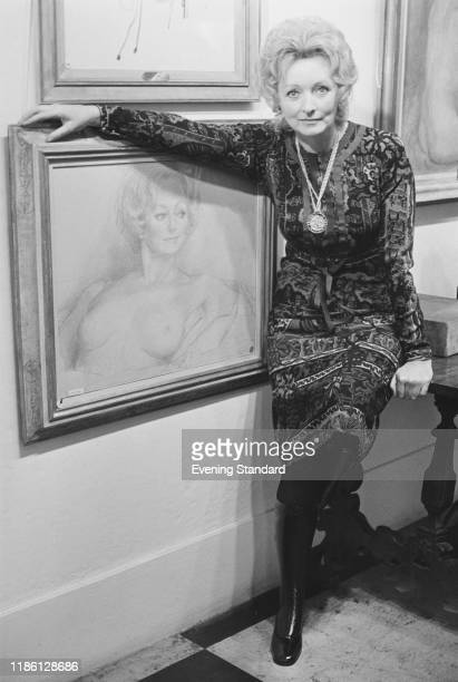 British costume designer Julie Harris posed with a portrait drawing of herself at a gallery in London on 3rd December 1970