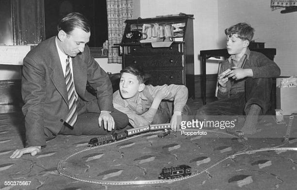 British cricket player Len Hutton and his sons Richard and John playing with a Hornby Dublo model train set at their home in Yorkshire 1956