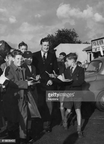 British cricketer Jim Laker signs autographs for young fans outside the Old Trafford ground in Manchester UK after a test match against Australia 1st...