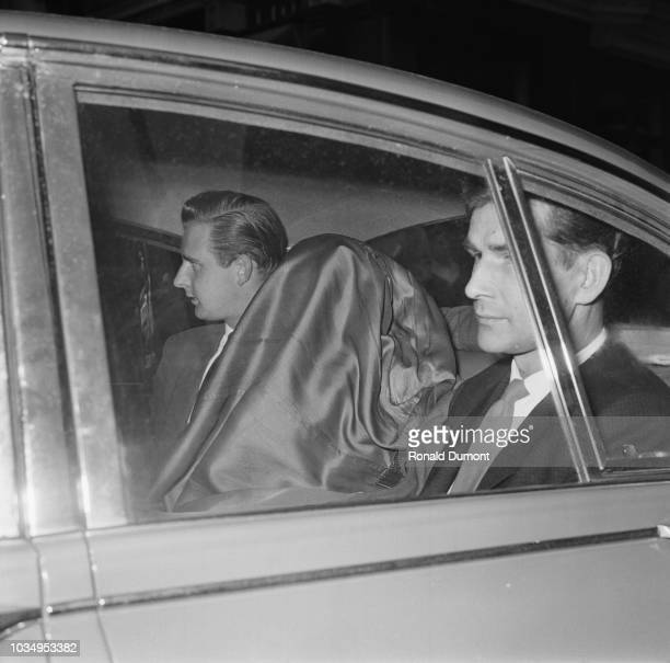 British criminal Charlie Wilson pictured with his head covered by a jacket seated between two detectives in the back of a police car as it leaves...