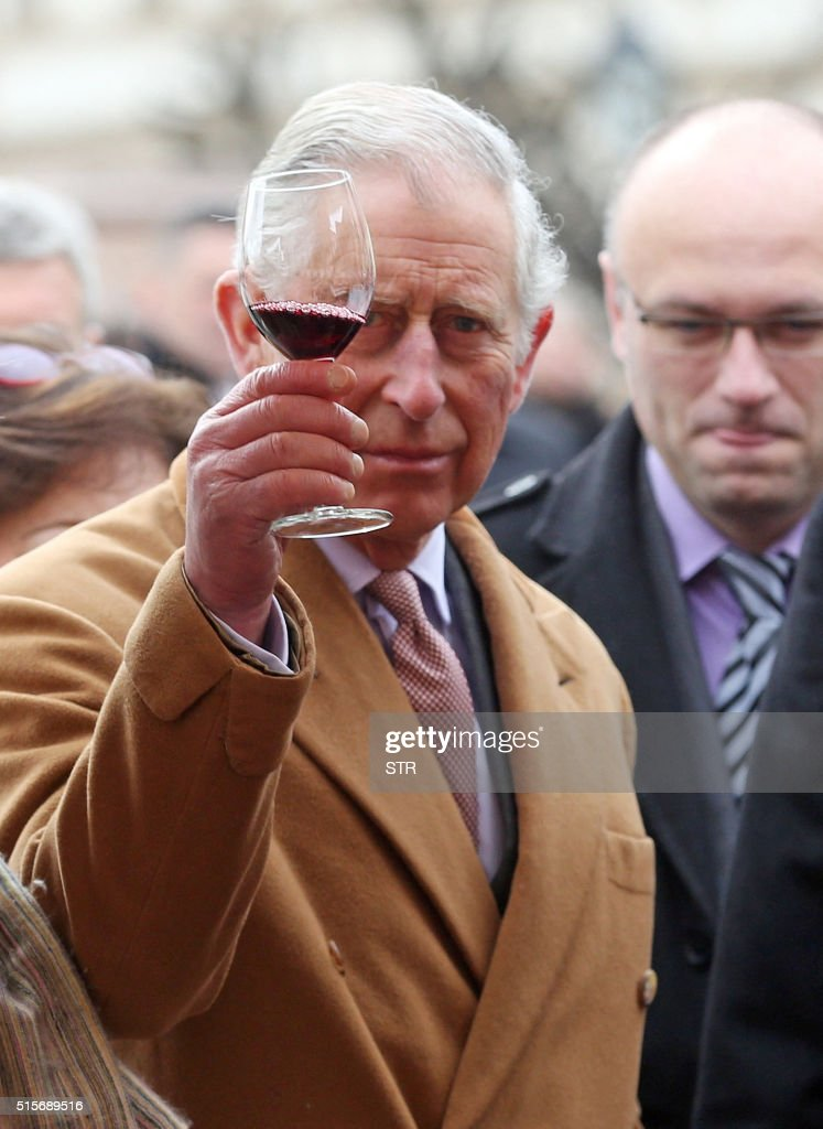 British Crown Prince Charles and his wife Camilla (unseen), the Duchess of Cornwall, taste local wines as they visit a market with traditional products on March 15, 2016 in Osijek. Prince Charles and his wife are on the last day of a two day visit to Croatia, part of a regional tour that will include Serbia, Montenegro and Kosovo. / AFP / STR
