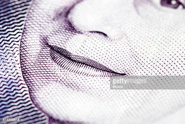 British currency closeup with Queen Elizabeth the second smile detail