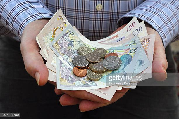 british currency in senior male's hands - british pound sterling note stock pictures, royalty-free photos & images
