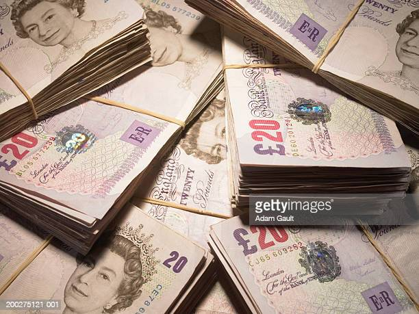 british currency: wads of twenty pound banknotes in pile, close-up - twenty pound note stock photos and pictures