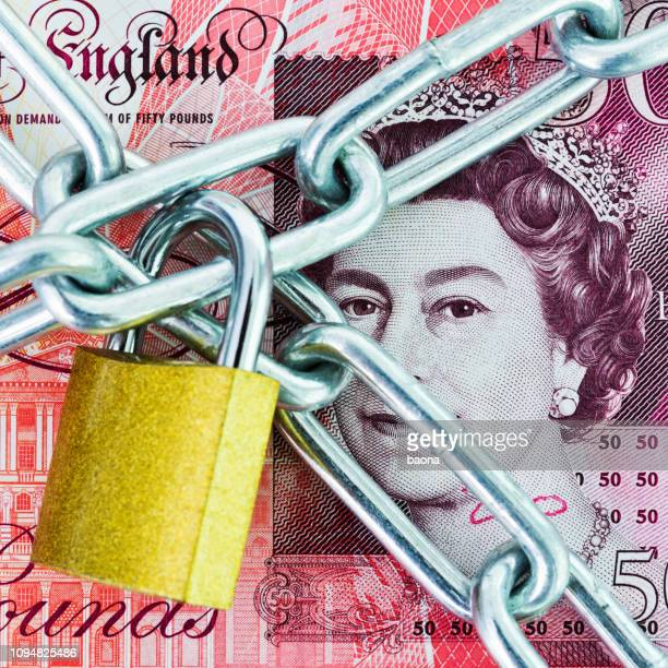 british currency with a chain and lock - fifty pound note stock pictures, royalty-free photos & images