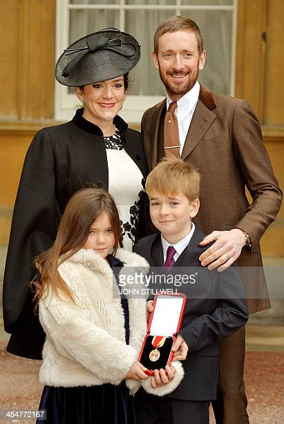 British cyclist Bradley Wiggins poses with his wife Catherine and children Isabella and Ben holding his medal after being appointed a Knights...