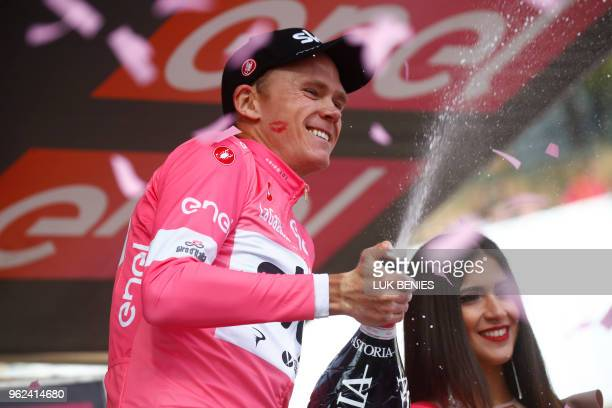 TOPSHOT British cyclist Christopher Froome celebrates as he wears the pink jersey on the podium after winning the 19th stage from Venaria Reale to...