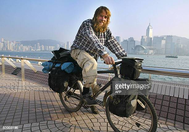 British cyclist Edward Genochio posees for the picture with his bike and belongings in front Hong Kong's Victoris harbour while he arrives in the...