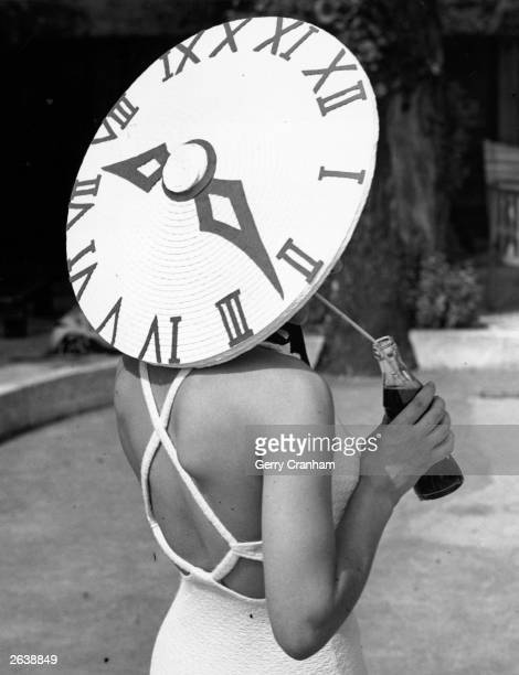 British dancer Rosemary Andree wearing a sunhat with a clock face design on a summer's day at the Roehampton Pool