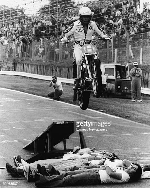 British daredevil Eddie Kidd jumps ten Radio One disc jockeys lain out upon the ground in a line with his motorcycle Brand's Hatch racing circuit...