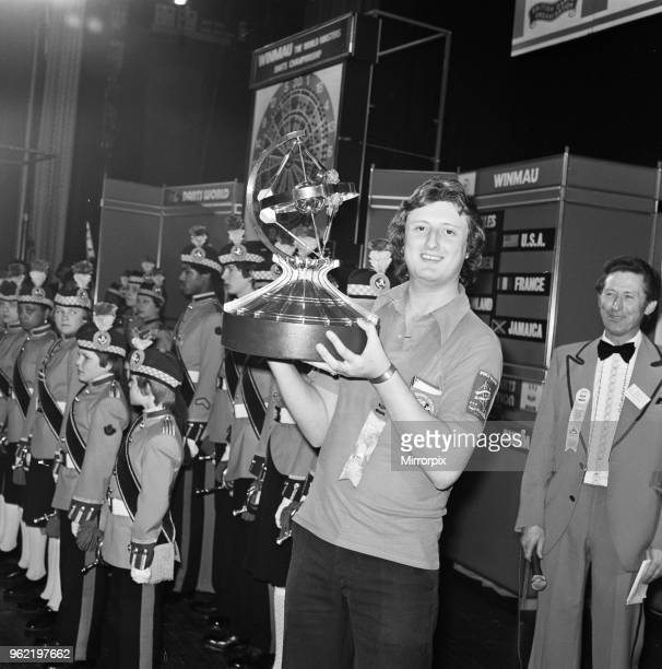 British dart player Eric Bristow holds aloft the trophy after winning the Worlds Masters Darts Championship at the Wembley Conference Hall for the...