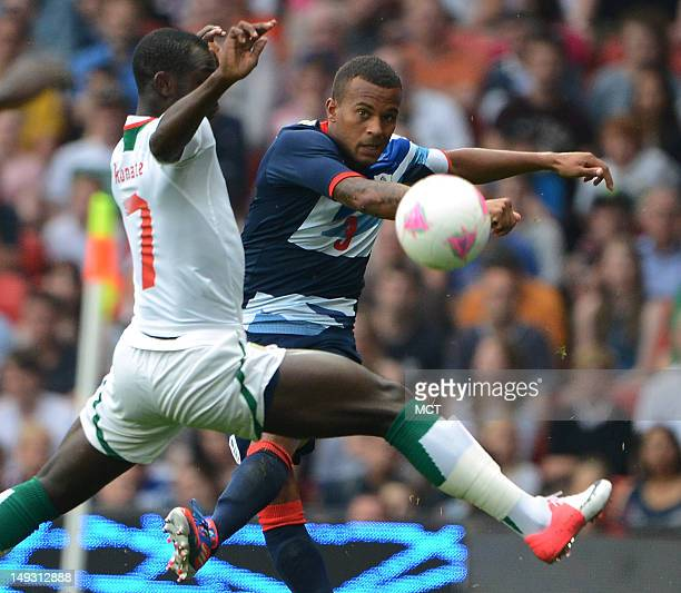British defender Ryan Bertrand passes around Senegal forward Moussa Konate in the first half at Old Trafford in Manchester England during the 2012...