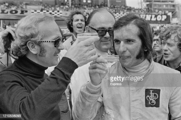British design engineer, and founder of Lotus Cars, Colin Chapman in conversation with Brazilian Formula One racing driver Emerson Fittipaldi during...