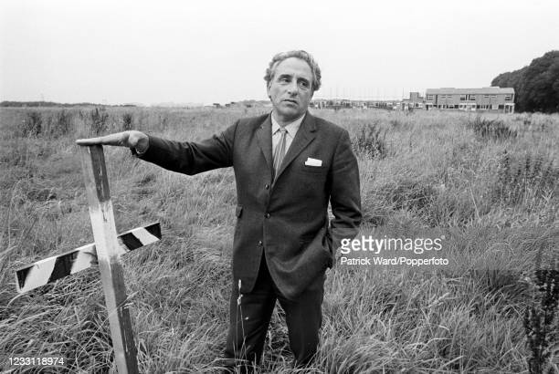 British designer and architect Eric Lyons standing in an empty field ,a future building site near Blackheath in London, circa June 1969. From a...