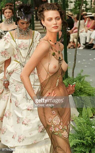British designer John Galliano showed this mermaidline sheath dress in antique gold tulle with an English garden style embroidery of pompom roses and...