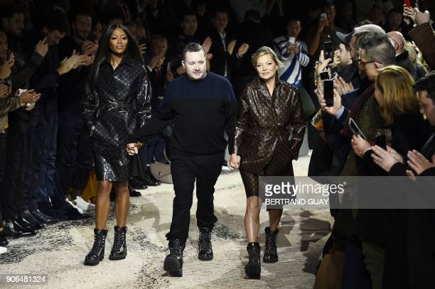British designer Kim Jones holds hands with British models Naomi Campbell and Kate Moss as he acknowledges the public at the end of the Louis Vuitton...