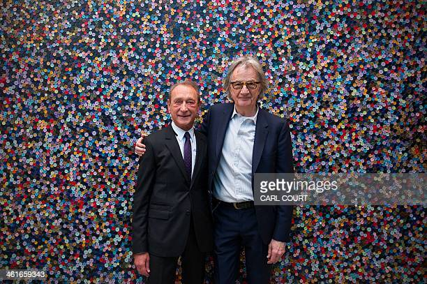 British designer Paul Smith poses for a photograph with the Paris Mayor Bertrand Delanoe next to a wall of buttons during the mayor's visit to the...